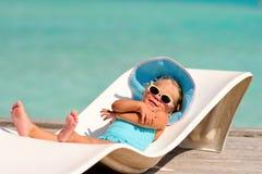 Kleines Mädchen, das im tropischen Ozeanhintergrund sich entspannt Lizenzfreie Stockfotografie