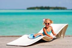 Kleines Mädchen, das im tropischen Ozeanhintergrund sich entspannt Lizenzfreie Stockbilder