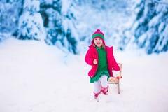 Kleines Mädchen, das im Wald des verschneiten Winters spielt Stockfotografie