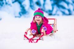 Kleines Mädchen, das im Wald des verschneiten Winters spielt Stockbild
