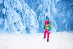Kleines Mädchen, das im Wald des verschneiten Winters spielt Stockfotos