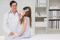 Kleines Mädchen, das Inhalator nimmt lizenzfreie stockbilder