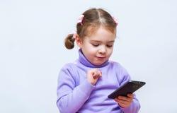 Kleines Mädchen, das intelligentes Telefon verwendet lizenzfreie stockfotos
