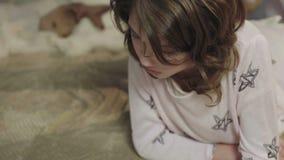Kleines Mädchen, das interessantes Buch über Abenteuer, glückliche Kindheit, Träume liest stock video footage