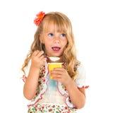 Kleines Mädchen, das Joghurt isst Getrennt auf weißem Hintergrund Stockbild