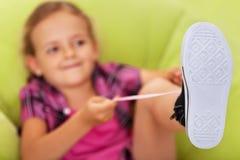 Kleines Mädchen, das kämpft, um ihre Schuhe zu binden lizenzfreies stockbild