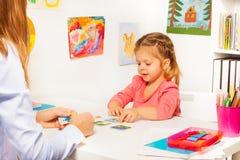 Kleines Mädchen, das Karten von der Tabelle in der Klasse nimmt Lizenzfreie Stockfotos