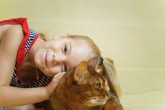 Kleines Mädchen, das Katze umarmt Lizenzfreies Stockfoto