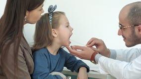 Kleines Mädchen, das Kehlprüfung mit Zungensenker durch einen männlichen Doktor hat stock video