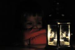 Kleines Mädchen, das Kerzenlicht in der Laterne betrachtet Stockfotos