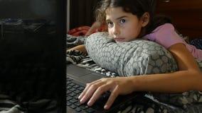 Kleines Mädchen, das Kind im Notizbuchonline-spiel-Laptop spielt stock video footage