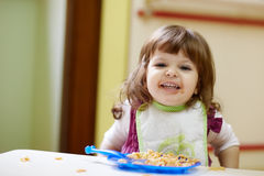 Kleines Mädchen, das am Kindergarten zu Mittag isst lizenzfreie stockfotografie
