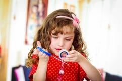 Kleines Mädchen, das Klebstreifen schneidet Stockfoto