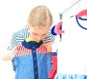Kleines Mädchen, das Kleid wählt Stockbild