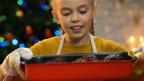 Kleines Mädchen, das kleine Kuchen im Backblech, stolz auf die Herstellung von Bonbons durch hält stock video footage