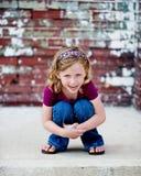 Kleines Mädchen, das Knie umarmt Lizenzfreie Stockbilder