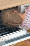 Kleines Mädchen, das Kopf in Spülmaschine setzt Stockfoto