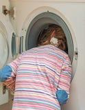 Kleines Mädchen, das Kopf in Waschmaschine setzt Lizenzfreie Stockfotografie