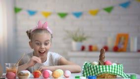 Kleines Mädchen, das langsam von unterhalb der Tabelle erscheint und bunte Ostereier bewundert stock footage