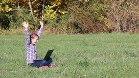 Kleines Mädchen, das Laptop im Park spielt stock video