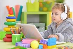 Kleines Mädchen, das Laptop und Kopfhörer verwendet Lizenzfreie Stockfotografie