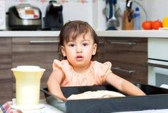 Kleines Mädchen, das Lebensmittel in der Küche kocht Stockfotografie