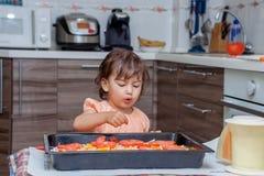 Kleines Mädchen, das Lebensmittel in der Küche kocht Stockfotos