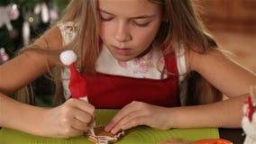 Kleines Mädchen, das Lebkuchenweihnachtsplätzchen verziert stock video