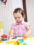 Kleines Mädchen, das Lehm formt Stockbild