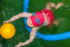 Kleines Mädchen, das lernt, in einem Pool zu schwimmen Lizenzfreie Stockfotografie