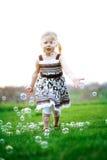 Kleines Mädchen, das Luftblasen jagt Stockfotografie