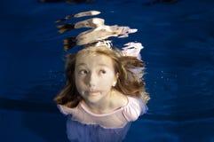 Kleines Mädchen, das lustiges Gesicht Unterwasser bildet lizenzfreies stockfoto