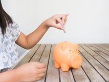 Kleines Mädchen, das Münze in Sparschwein für die Rettung mit Stapel von setzt Stockfotos