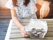 Kleines Mädchen, das Münze in Sparschwein für die Rettung mit Stapel von setzt Stockfotografie