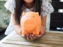 Kleines Mädchen, das Münze in Sparschwein für die Rettung mit Stapel von setzt Stockbilder