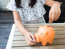 Kleines Mädchen, das Münze in Sparschwein für die Rettung mit Stapel von setzt Lizenzfreies Stockbild