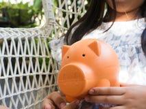 Kleines Mädchen, das Münze in Sparschwein für die Rettung mit Stapel von setzt Lizenzfreies Stockfoto