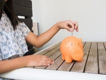 Kleines Mädchen, das Münze in Sparschwein für die Rettung mit Stapel von setzt lizenzfreie stockfotografie