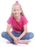 Kleines Mädchen, das mit überkreuzten Beinen sitzt Lizenzfreies Stockfoto