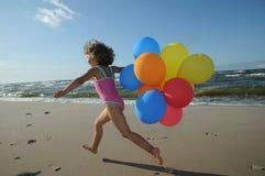 Kleines Mädchen, das mit Ballonen auf dem Strand spielt Lizenzfreies Stockfoto