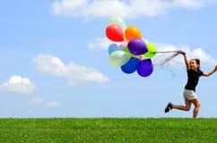 Kleines Mädchen, das mit Ballonen läuft lizenzfreie stockbilder