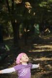 Kleines Mädchen, das mit Blättern spielt Stockbild