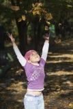 Kleines Mädchen, das mit Blättern spielt Lizenzfreies Stockfoto