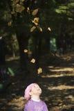 Kleines Mädchen, das mit Blättern spielt Lizenzfreie Stockfotografie