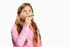 Kleines Mädchen, das mit Bleistift in ihrem Mund denkt stockfotografie