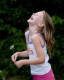 Kleines Mädchen, das mit Blume lacht Stockfotografie