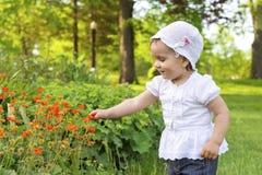 Kleines Mädchen, das mit Blumen spielt Stockbilder