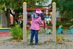 Kleines Mädchen, das mit buntem hölzernem Abakus auf Spielplatz spielt Stockfotos