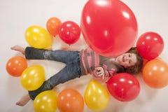 Kleines Mädchen, das mit bunten Ballonen spielt stockfoto