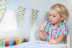 Kleines Mädchen, das mit bunten Bleistiften zuhause zeichnen spielt Stockfotos